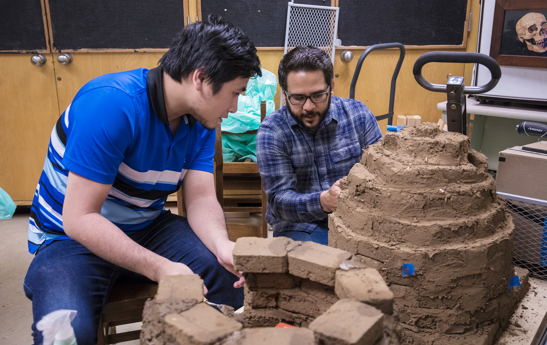 Two students work on an oven made of adobe bricks