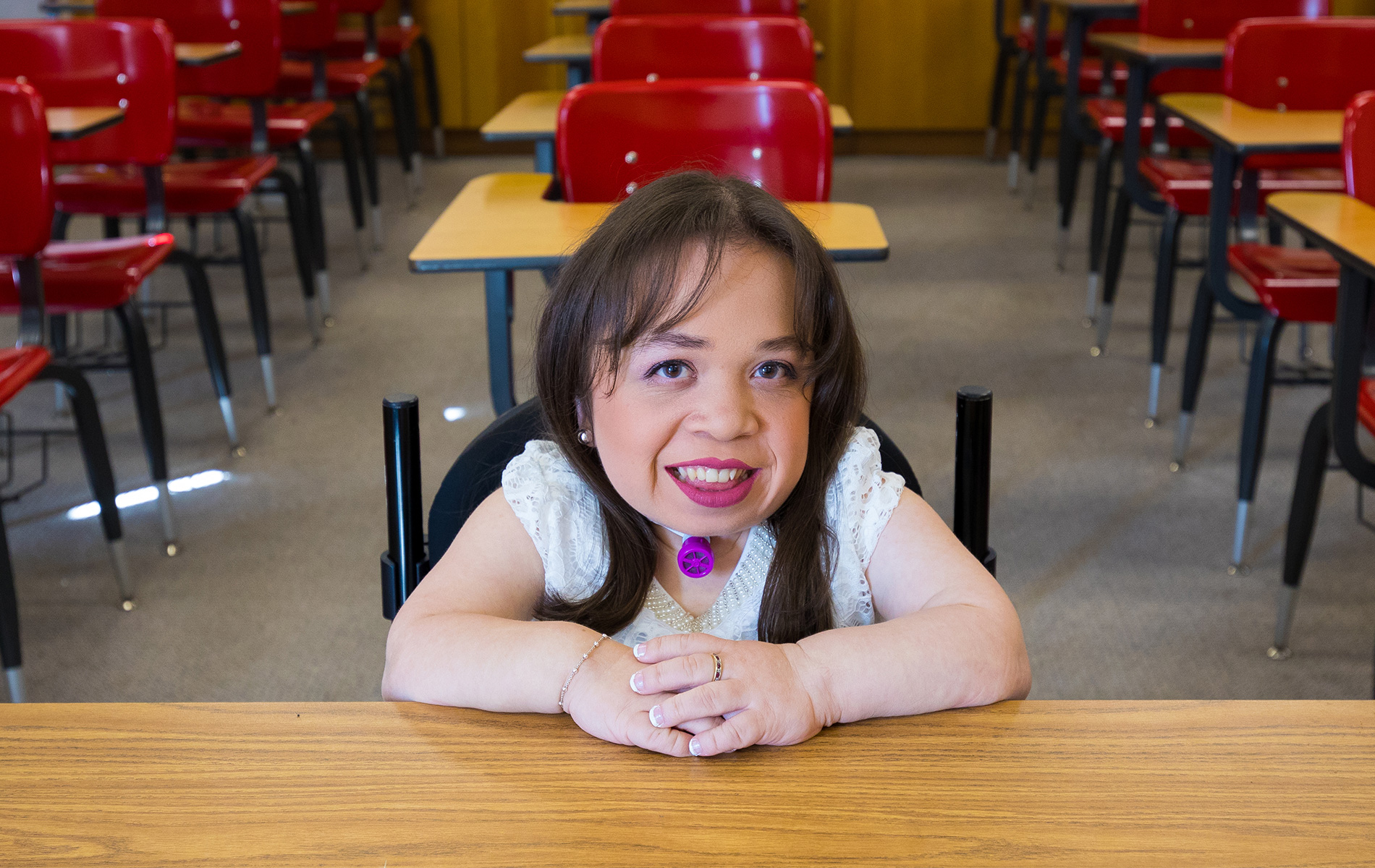 Student Isabel Bueso, who has a rare disease, poses with her hands on top of each other at a desk in a classroom