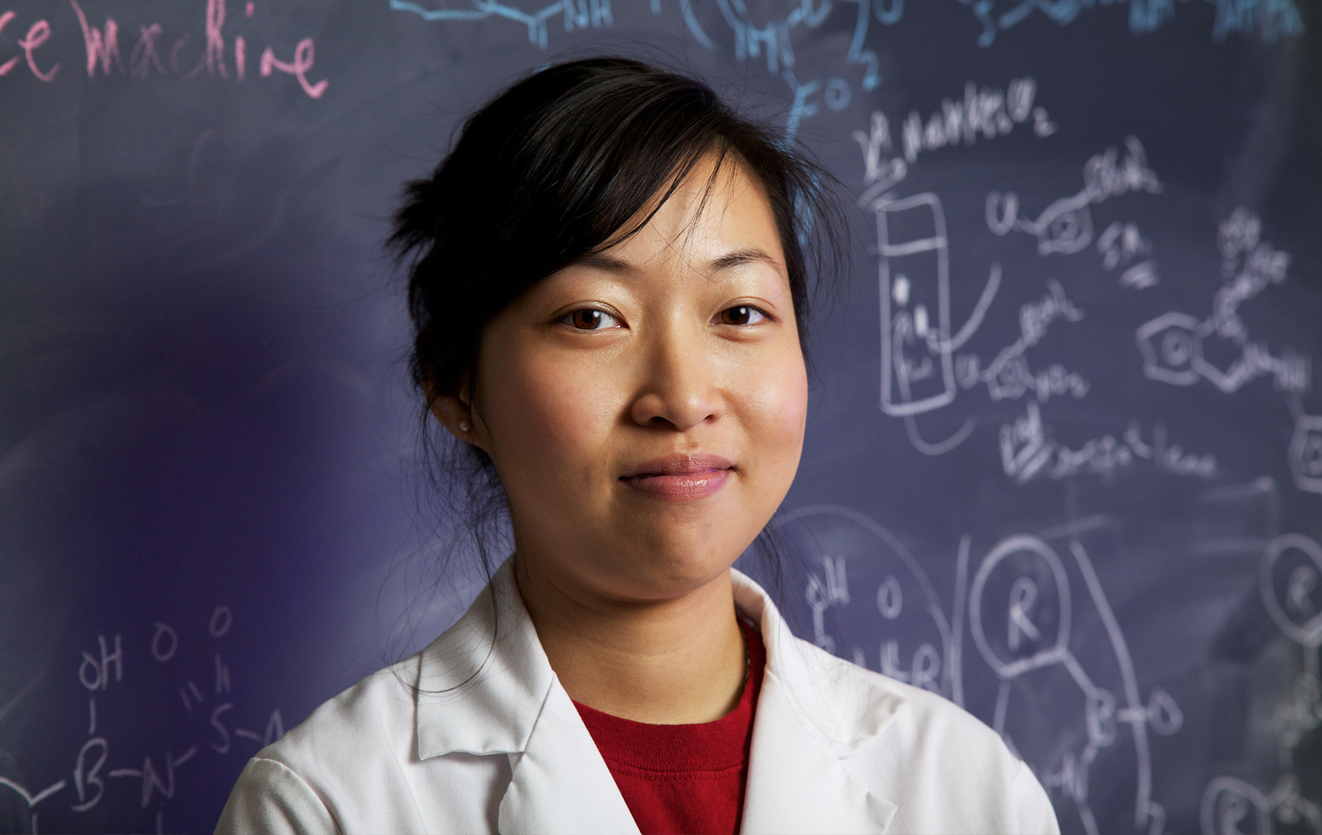 Mindy Tong stands in a lab coat in front of a chalkboard
