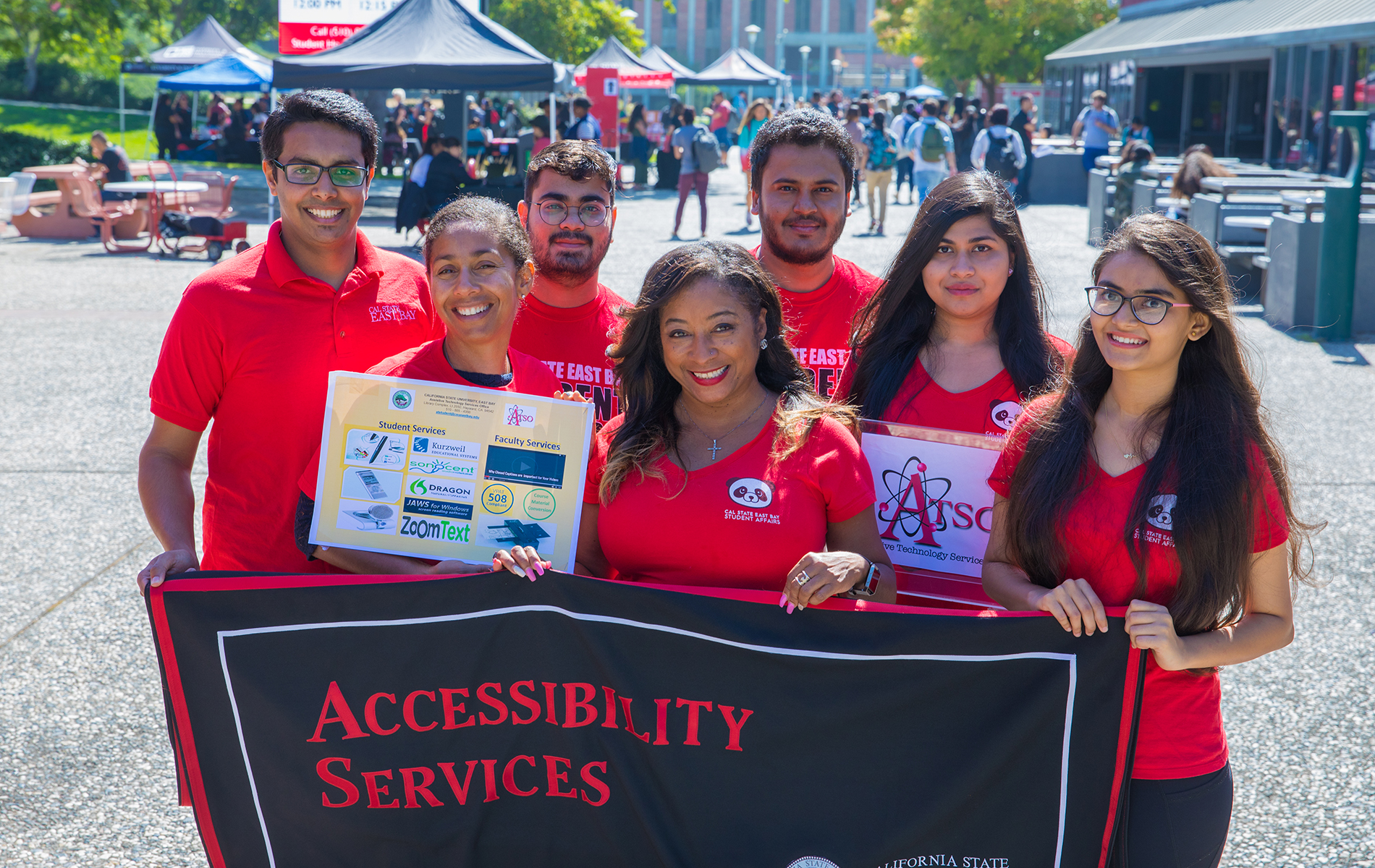 "Group of young adults wearing red shirts hold a sign that says ""accessibility services"" outside the CSUEB bookstore."