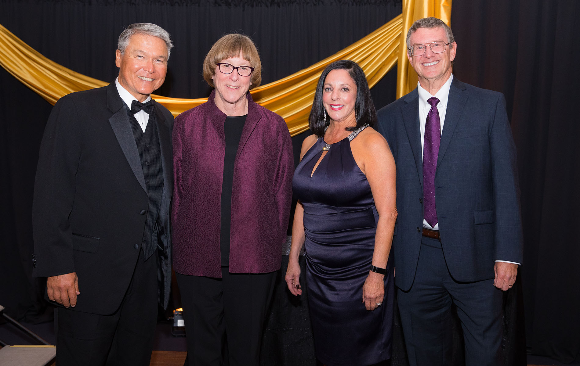 Four alumni, two men and two women, pose at a gala event