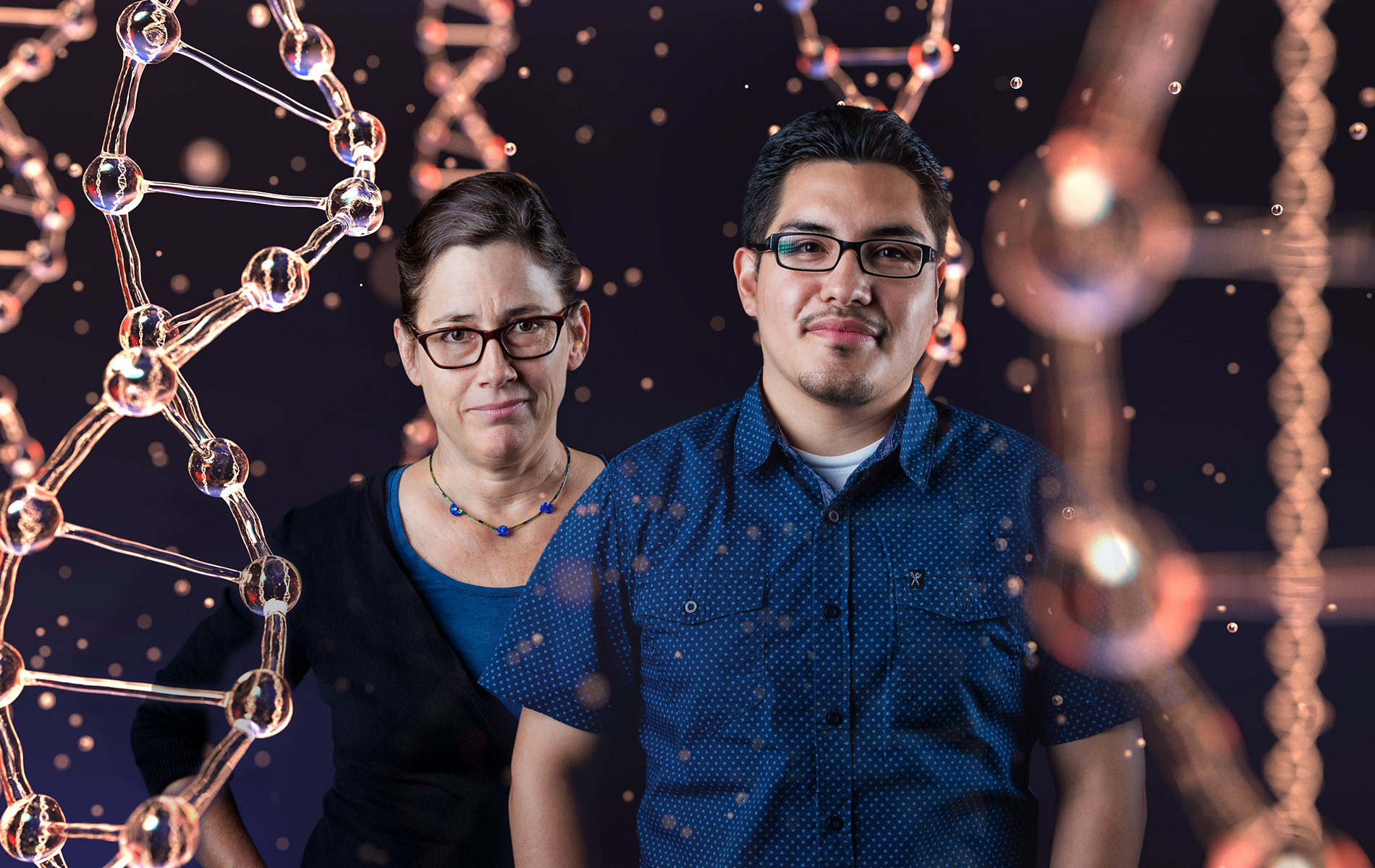 Two people posing with DNA in the background