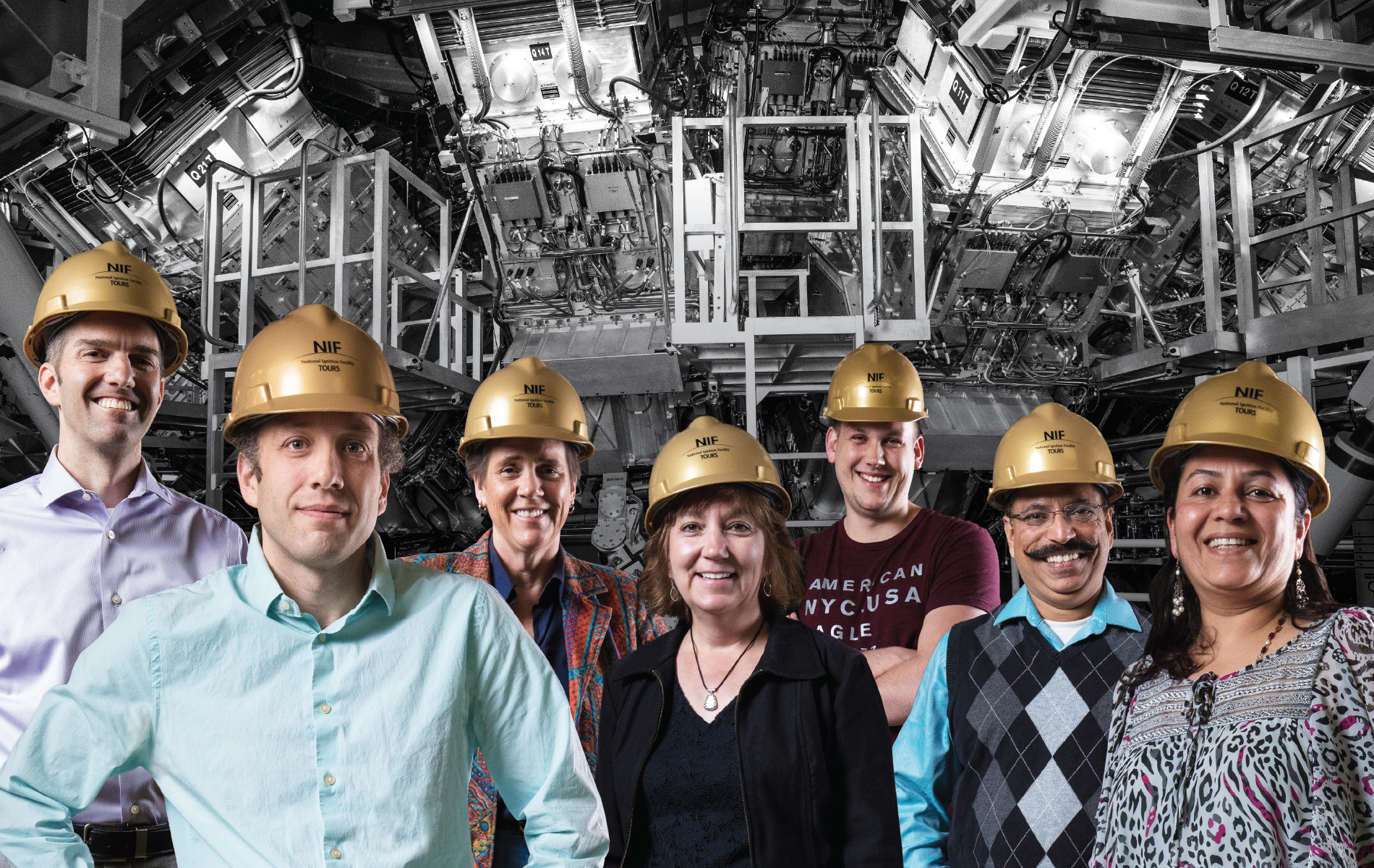 Scientists in gold construction caps pose in front of machinery