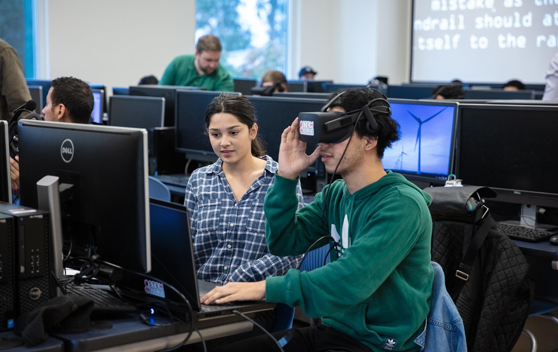 A male student looks at a computer with VR googles on, while a female student watches