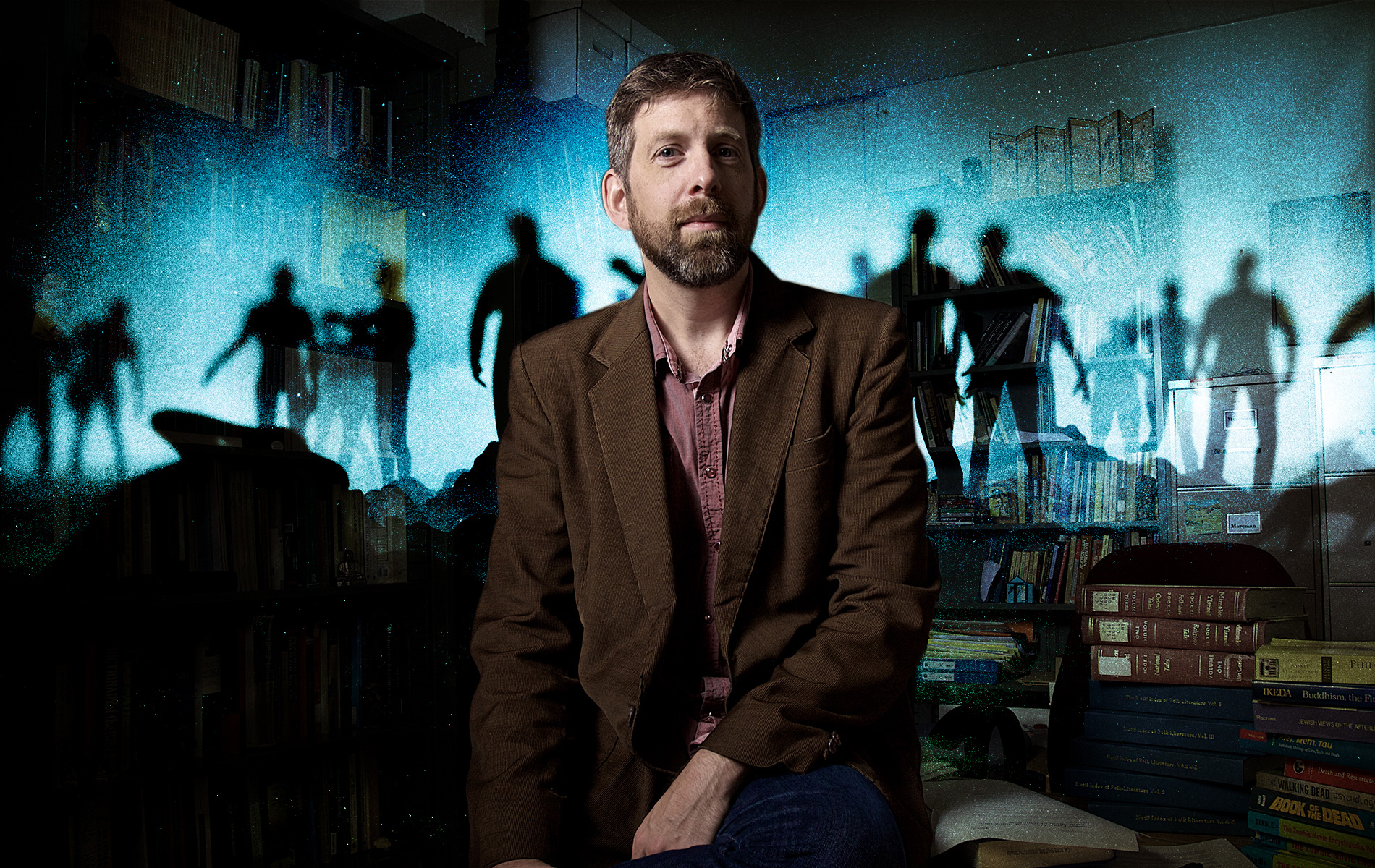 Professor Christopher Moreman sits with zombies silhouetted in the background