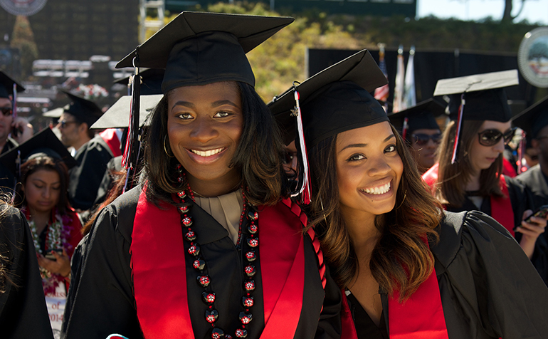 Two females students pose at a graduation ceremony.