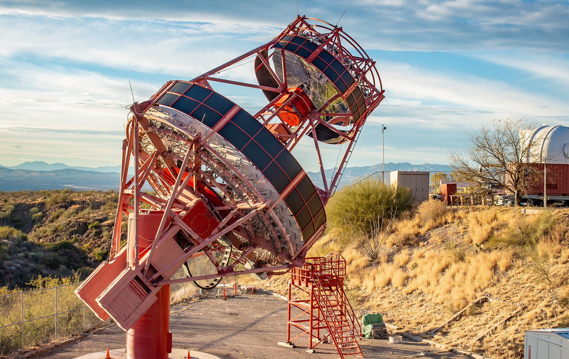A large red telescope with desert landscape in the background