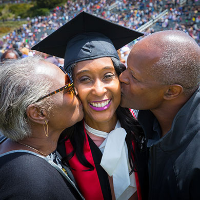 A student in cap in gown is kissed on her cheeks by her parents