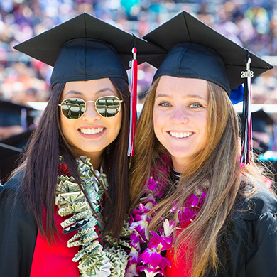 Two female students in grad cap, gown, and leis pose at graduation