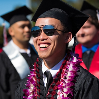 A student celebrates on stage after receiving his diploma