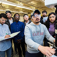 A diverse group of students huddle around science equipment