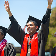 A student raises is hands in celebration at graduation