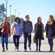 A diverse group of students walks through campus