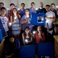 A group of students hold lightbulbs