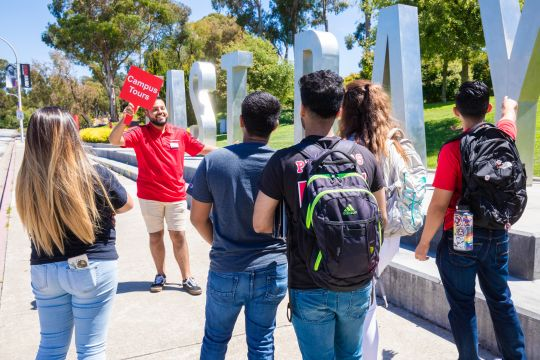 Picture of campus tour with students standing in front of the East Bay Letters