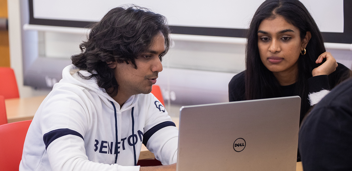 Two students looking at laptop together