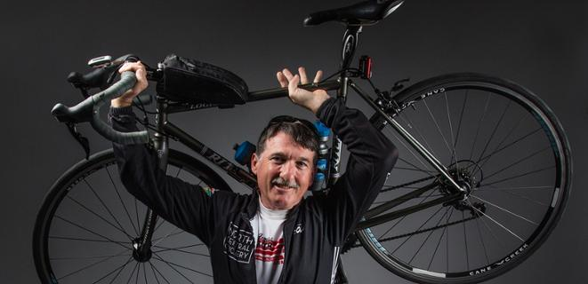 Paul Carpenter holds a bike over his head