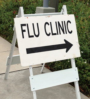 Photo of a white directional sign for a flu clinic.