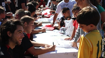 Photo of CSUEB soccer players greeting children and signing autographs.