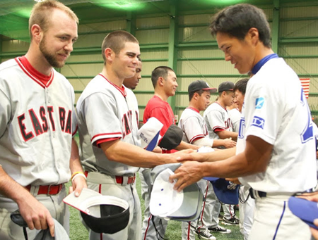 Photo of baseball players from CSUEB and FIT exchanging baseball hats.