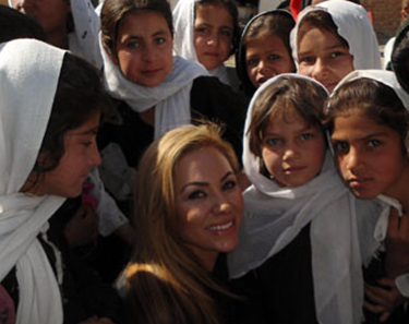 Photo of CSUEB alumna Shakira Niazi '93 with girls in her native Afghanistan.