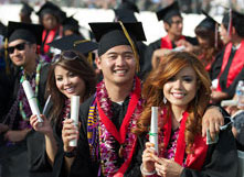 Image of CSUEB graduates holding their diplomas at a commencement ceremony.