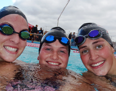 Photo of three female swimmers in a pool smiling with caps and goggles.