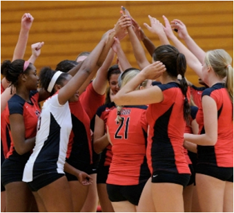 Photo of the CSUEB volleyball team cheering before a game.