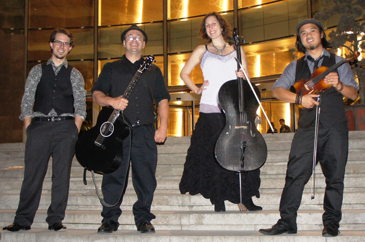 Image of the musical group Dirty Cello standing on the outside stairs of a concert hall.