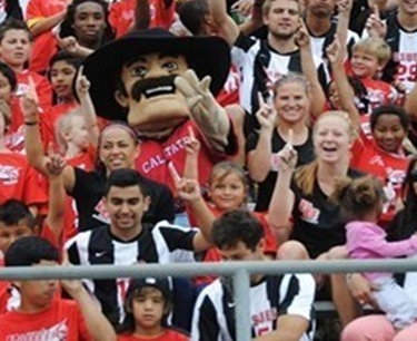 Photo of youth soccer players with CSUEB Pioneer Pete in University's stadium.