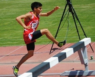 Photo of Daniel Damian jumping over a hurdle during the CCAA steeplechase event.