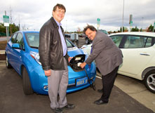 professor and provost plug charging cord into electric vehicle