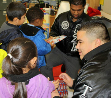 two CSUEB students giving toys to elementary school children.( courtesy of Bernardo Godinez)