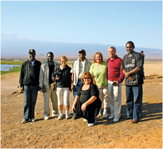 A research trip to interview managers at Kenyan hotels took three CSUEB faculty members to the south and Amboseli National Park. Pictured, from left: Walter Otieno, Richard Makopondo, a visiting professor from Sweden, Titus Bagadja, Judy Gillani, Bijan Gillani, Jack Mtula, and Melany Spielman (seated). Mt Kilimanjaro appears in the background.