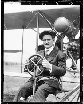 Vintage photo of Lincoln Beachey sitting in a Curtiss stunt plane.
