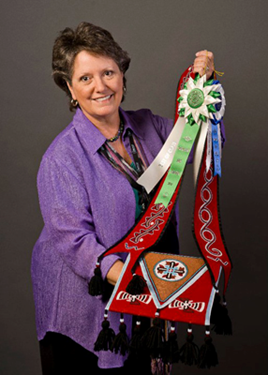 Photo of Martha Berry holding Cherokee beadwork.