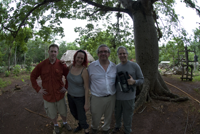 Four people in front of a tree.