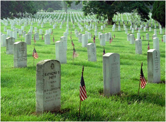 Photo at Arlington Memoria Cemetery of grave sites draped with American flags.