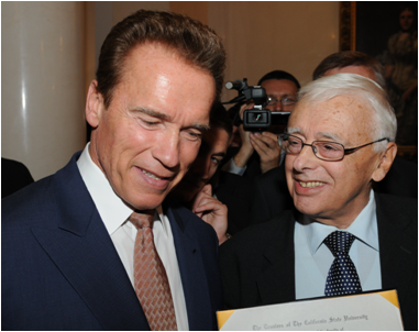Edvard Goyzman (r) showing California Governor Arnold Schwarzenegger the Moscow MBA diploma the governor signs for all graduates.