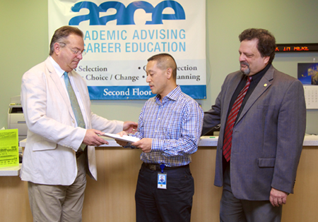 Photo of Scott Louie handing a check to Larry Bliss of the CSUEB career center.