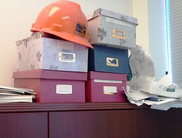 Photo of a messy desk with hard hat, boxes and papers.