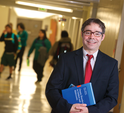 Image of Dr. Stephen Morewitz in a school hallway.