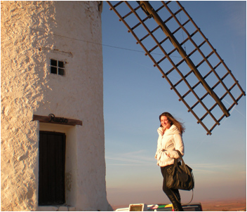 Photo of a college student in front of the windmills of La Mancha in Spain.