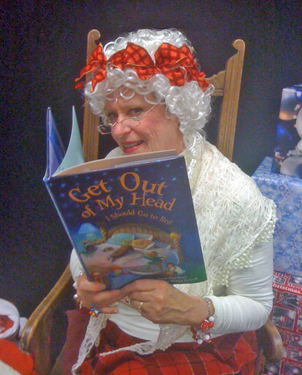 """Mrs. Claus (Susan Pace-Koch '04) reads to children from her first book, """"Get Out of My Head, I Should Go to Bed"""" (courtesy of Susan Pace-Koch"""