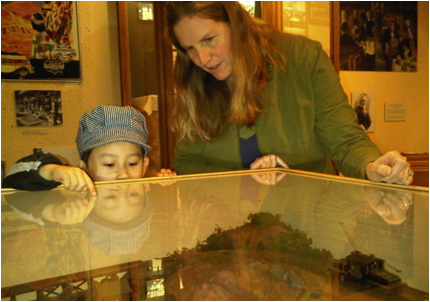 Marjorie Rhodes-Ousley helps Kenji, 4, look at a model railroad display. by: Kristofer Noceda