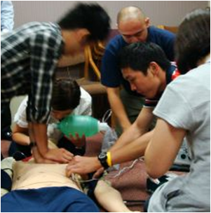Photo of students working on a cardiac training dummy.