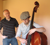 Man with son who is playing the string bass.