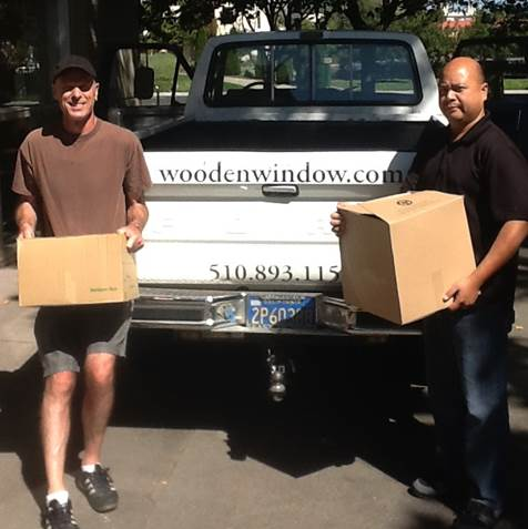 Image of Dr. Lee and Vince Ang standing in front of a pick-up truck loaded with boxes of donated of textbooks.