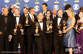 group of Daily Show writers, including JR Havlan at left and host Jon Stewart at center, holding Emmy award statues