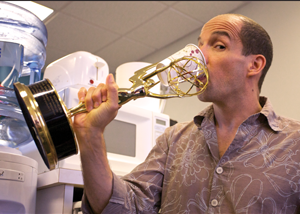 JR Havlan drinks from a paper cup inserted in one of his Emmy statues.